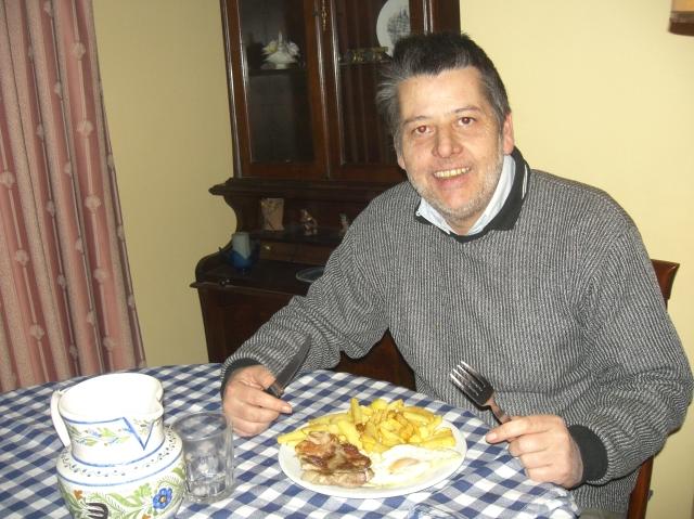 cenando huevos fritos con patatas en la mesa