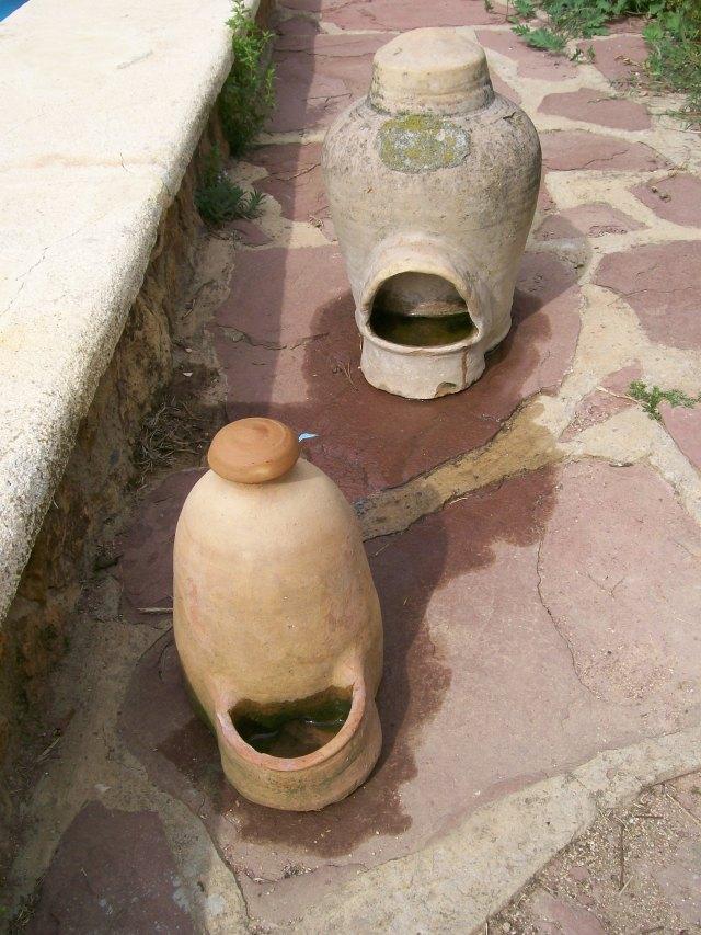 Dos bebederos antiguos con agua para los pájaros.